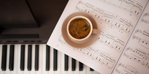 Coffee cup on the piano with notes